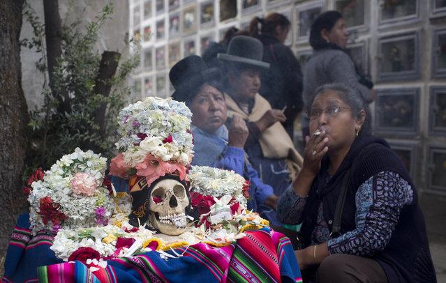 "Women sit with a decorated human skull or ""natitas"", during the Natitas Festival celebrations, in La Paz, Bolivia, Tuesday, November 8, 2016. (Photo by Juan Karita/AP Photo)"