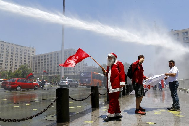A demonstrator dressed as Santa Claus holds up a flag as a riot police vehicle releases a jet of water during a protest against the private system of pension fund administrators in Santiago, Chile, December 10, 2015. (Photo by Ivan Alvarado/Reuters)