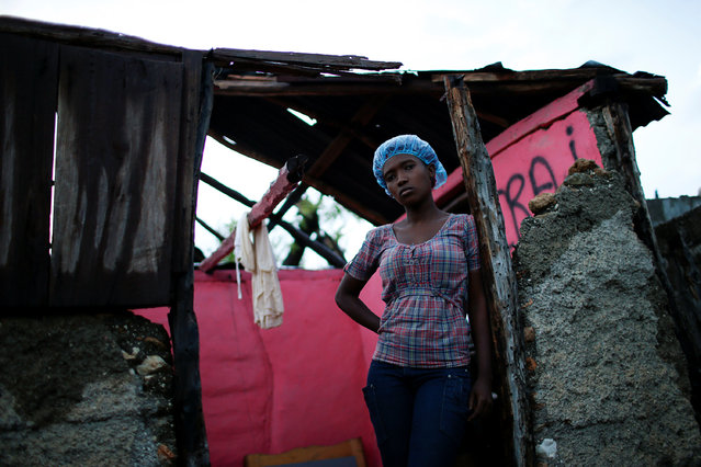 "Carine Louis-Jean, 22, poses for a photograph in her destroyed house after Hurricane Matthew hit Jeremie, Haiti, October 17, 2016. ""The roof of my house is completely gone and some of walls were destroyed. I have lost everything I had, but I thank God that I have a friend who is letting me stay at her house. I could say I'm lucky, because none of my family died during the hurricane, but I do not think I'm lucky"", said Louis-Jean. (Photo by Carlos Garcia Rawlins/Reuters)"