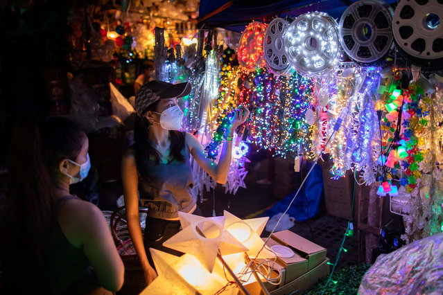 Shoppers wearing face masks for protection against the coronavirus disease (COVID-19) look at Christmas lights for sale at a market in Quezon City, Metro Manila, Philippines, December 7, 2020. (Photo by Eloisa Lopez/Reuters)