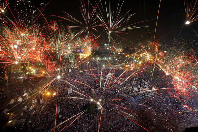 """Fireworks light the sky opponents of Egypt's Islamist President Mohammed Morsi celebrate in Tahrir Square in Cairo, Egypt, Wednesday, July 3, 2013. A statement on the Egyptian president's office's Twitter account has quoted Mohammed Morsi as calling military measures """"a full coup"""". The denouncement was posted shortly after the Egyptian military announced it was ousting Morsi, who was Egypt's first freely elected leader but drew ire with his Islamist leanings. The military says it has replaced him with the chief justice of the Supreme constitutional Court, called for early presidential election and suspended the Islamist-backed constitution.(Photo by Amr Nabil/AP Photo)"""