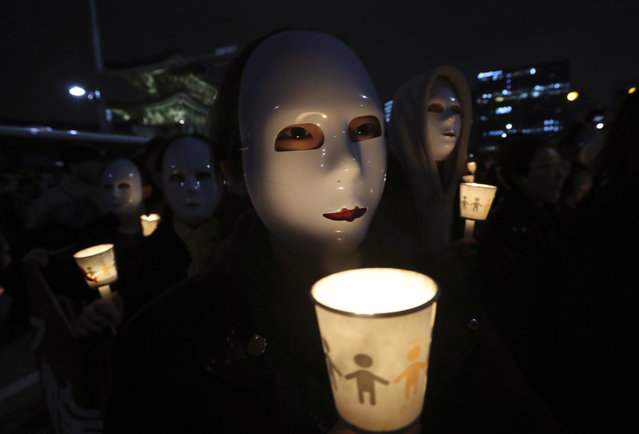 South Korean college students wearing masks hold up candles as they march after a rally calling for South Korean President Park Geun-hye to step down in Seoul, South Korea, Saturday, November 12, 2016. Hundreds of thousands of people flooded Seoul's streets on Saturday demanding the resignation of Park amid an explosive political scandal, in what may be South Korea's largest protest since it shook off dictatorship three decades ago. (Photo by Lee Jin-man/AP Photo)