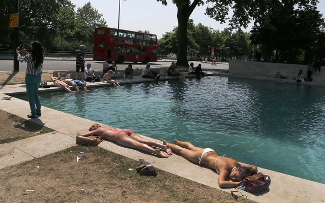 People enjoy the sun near a fountain at Hyde Park in London, Monday, July 8, 2013. England's capital experienced the warmest days of the year with temperatures up to 29 Celsius (84 Fahrenheit). (Photo by Frank Augstein/AP Photo)