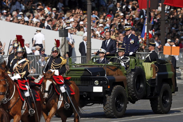 France's President Francois Hollande stands at attention in the command car as he reviews the troops while descending from the Champs Elysees at the start of the traditional Bastille Day military parade in Paris July 14, 2013. (Photo by Benoit Tessier/Reuters)
