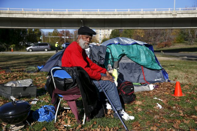 "Owen Makel, 65, who has been homeless for nearly 14 years and has lived at the camp for four months, sits by his tent between the Watergate and Whitehurst Freeway in Washington D.C., November 16, 2015. ""You have to understand this: we people as homeless have lives, just like you all have lives. We don't want to be out on the street but we don't have an alternative. People have no other place to go"", Makel said. (Photo by Shannon Stapleton/Reuters)"