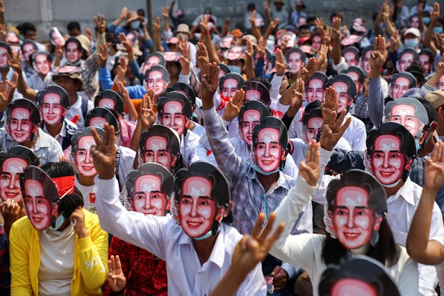 Protesters wearing masks depicting ousted leader Aung San Suu Kyi, flash three-finger salutes as they take part in a protest against the military coup in Yangon, Myanmar, February 28, 2021. (Photo by Reuters/Stringer)
