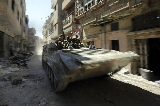 Soldiers of the Syrian government forces patrol on a tank in a devastated street on July 31, 2013 in the district of al-Khalidiyah in the central Syrian city of Homs. The Syrian government announced the capture of Khalidiyah, a key rebel district in Homs, Syria's third city and a symbol of the revolt against President Bashar al-Assad. (Photo by Joseph Eid/AFP Photo)