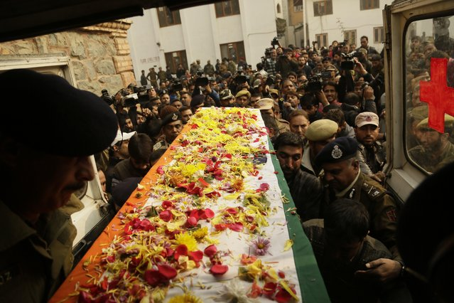 Indian police officers carry the coffin of their colleague who was killed in a shootout, at the police headquarters in Srinagar, Indian controlled Kashmir, Wednesday, November 16, 2016. Policeman Mohd Shafi Dar was killed early Wednesday in a shootout with suspected militants in Sopore, according to media reports. (Photo by Mukhtar Khan/AP Photo)