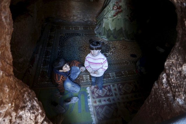 Internally displaced Syrian children stand at the entrance of their makeshift shelter that is an underground cave in Om al-Seer, southern Idlib countryside, Syria December 26, 2015. (Photo by Khalil Ashawi/Reuters)