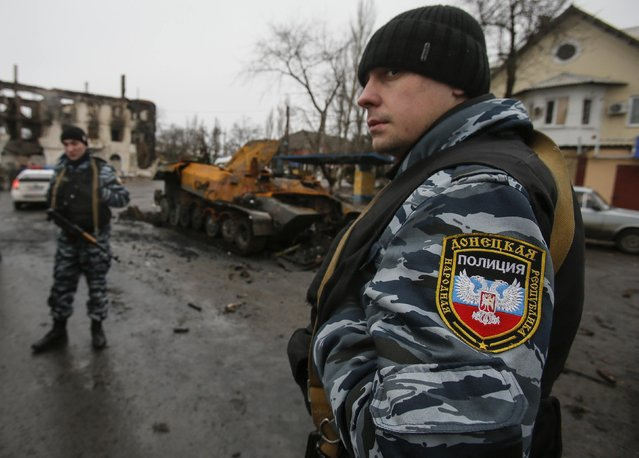 Members of the police of the separatist self-proclaimed Donetsk People's Republic gather near a burnt-out armoured vehicle in Vuhlehirsk, Donetsk region February 6, 2015. The rebels have been concentrating on Debaltseve, a rail hub where a government garrison has held out despite being nearly encircled. (Photo by Maxim Shemetov/Reuters)