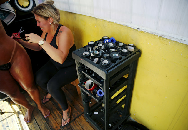 Erika, owner of the Erika Bronze spa, puts a masking tape bikini on a woman's body before sunbathing on a terrace to have the perfect bikini line ('marquinha' in Portuguese), in Rio de Janeiro, Brazil, November 17, 2016. (Photo by Pilar Olivares/Reuters)