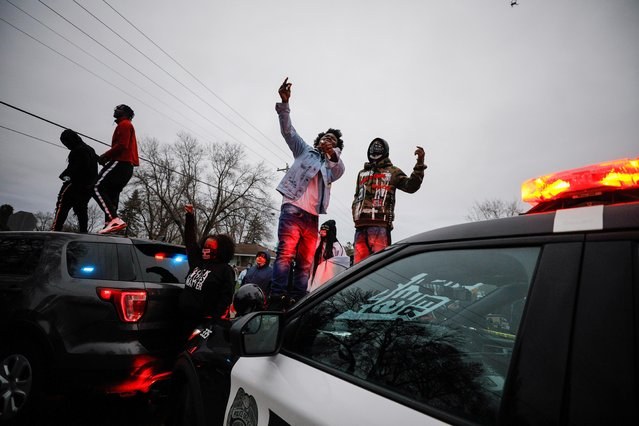 Demonstrators stand on a police vehicle during a protest after police allegedly shot and killed a man, who local media report is identified by the victim's mother as Daunte Wright, in Brooklyn Center, Minnesota, U.S., April 11, 2021. (Photo by Nick Pfosi/Reuters)
