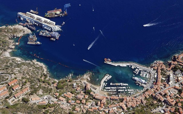 An aerial view shows the Costa Concordia as it lies on its side next to Giglio Island taken from an Italian navy helicopter, on September 12, 2013. (Photo by Alessandro Bianchi/Reuters)