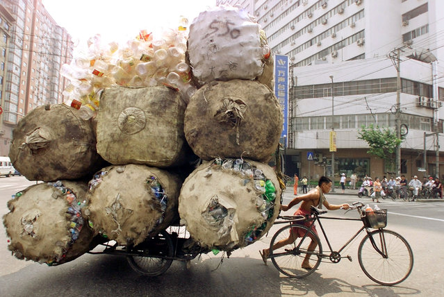 An enterprising Chinese man pulls a bicycle cart packed high with bags of recyclable plastic containers in Shanghai July 25, 2002. The man sells each kilogram (2.2 pounds) of plastic for 0.08 yuan ($.01) to a nearby depot. (Photo by Claro Cortes IV/Reuters)