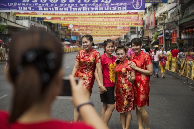 Women wearing traditional red clothes celebrating the Chinese Lunar New Year have their picture taken in Bangkok's Chinatown February 19, 2015. (Photo by Damir Sagolj/Reuters)