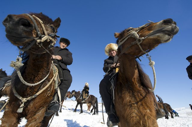 Herders ride horses at a winter festival in Yining, Xinjiang Uighur Autonomous Region, China, January 10, 2016. (Photo by Reuters/China Daily)