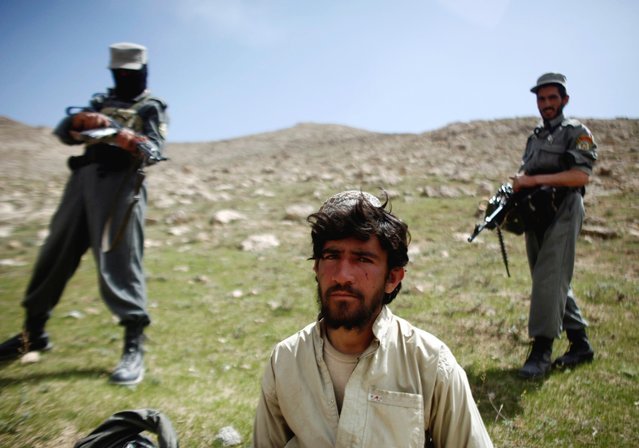 Afghan policemen stand next to a captured Taliban fighter after a gun battle near the village of Shajoy in Zabol province, March 2008. (Photo by Goran Tomasevic/Reuters)