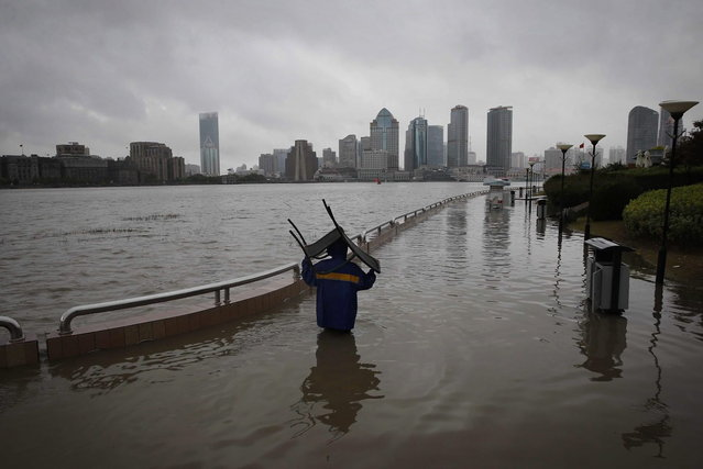 A person carries a chair through a flooded riverside park in Shanghai, China, Monday, October 7, 2013. A typhoon slammed into southeastern China on Monday with powerful winds and heavy rains that killed at least five people, cut power, canceled flights and suspended train services. (Photo by AP Photo)