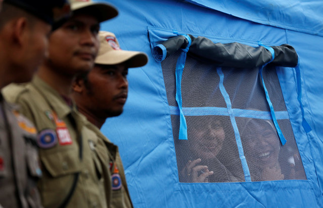 Women look out from a tent while waiting for Indonesian President Joko Widodo to walk by on the grounds of a collapsed mosque following this week's earthquake in Pidie Jaya, Aceh province, Indonesia December 9, 2016. (Photo by Darren Whiteside/Reuters)