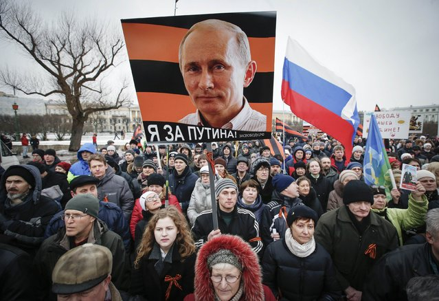 "A photo of Russia's President Vladimir Putin is seen on a poster as people attend an ""Anti-Maidan"" rally to protest against the 2014 Kiev uprising, which ousted President Viktor Yanukovich, in St.Petersburg February 21, 2015. REUTERS/Maxim Zmeyev  (RUSSIA - Tags: POLITICS CIVIL UNREST)"