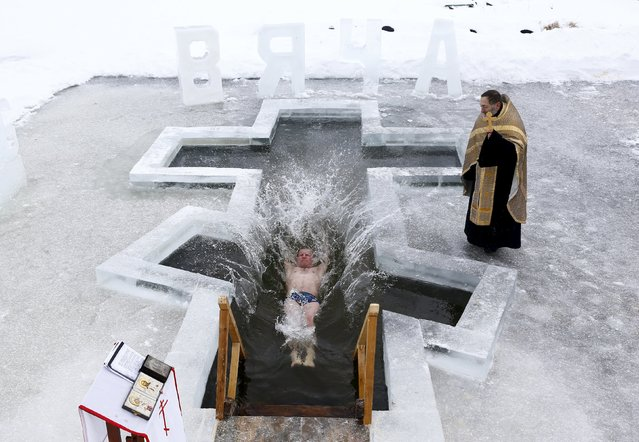 A man dips into the icy waters of a lake as part of celebrations for Orthodox Epiphany on the outskirts of Minsk, January 18, 2016. Orthodox believers will mark Epiphany on January 19 by immersing themselves in icy waters regardless of the weather. (Photo by Vasily Fedosenko/Reuters)