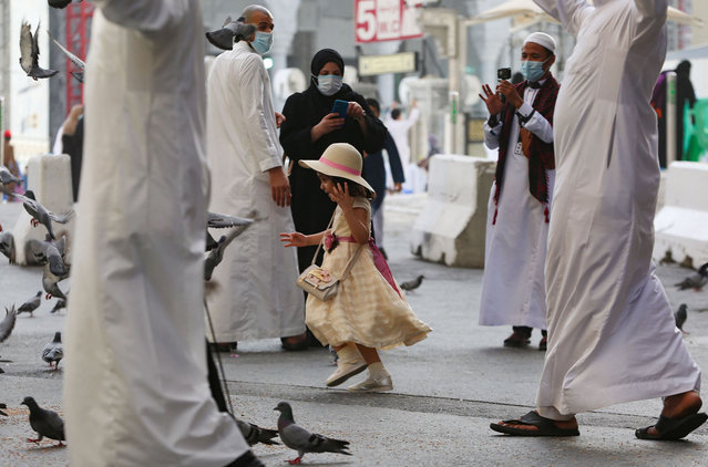 A young girl chases pigeons as Muslim worshippers gather to perform the Eid al-Fitr morning prayer at the Grand Mosque in Saudi Arabia's holy city of Mecca to mark the end of the fasting month of Ramadan, on May 13, 2021. (Photo by Abdulghani Essa/AFP Photo)