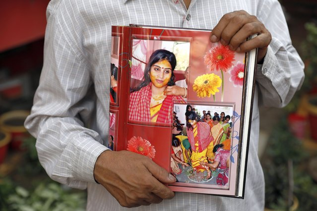 Radha Gobindo Pramanik holds photographs of his daughter who died of COVID-19 in Lucknow, India, Thursday, June 3, 2021. Two months ago Pramanik and his wife threw a party to celebrate their daughter's pregnancy and the upcoming birth of their long-awaited grandchild. Within days, his wife, his daughter and his unborn grandchild were all dead, among the tens of thousands killed as the coronavirus ravaged India in April and May. (Photo by Rajesh Kumar Singh/AP Photo)