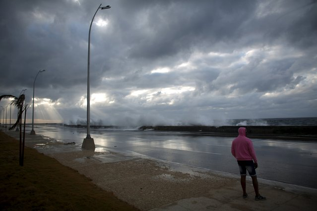 A man watches waves breaking at the seafront Malecon in Havana, January 24, 2016. Havana's seafront Malecon continued to be slammed by massive waves that flooded parts of the seaside city on Sunday. As a result, Havana was confronting flooding as a cold front passes through the Caribbean island. The giant waves began washing up onto shore during sunrise. The waves have been accompanied by winds passing through at a speed between 35 and 50 km (21 to 31 miles) per hour. (Photo by Alexandre Meneghini/Reuters)