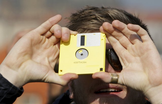 A man watches a partial solar eclipse looking through a floppy disc from the medieval Charles Bridge in Prague March 20, 2015. (Photo by David W. Cerny/Reuters)