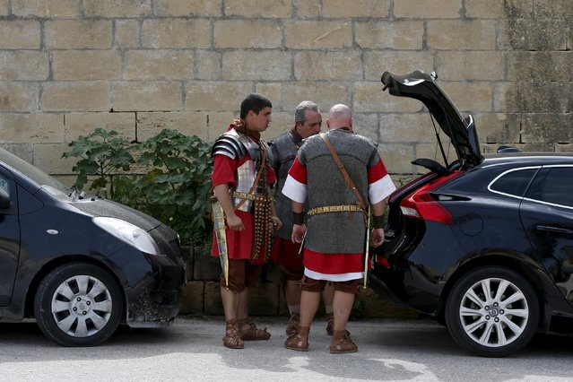 Members of the Legio X Fretensis (Malta) re-enactment group stand next to their car while preparing for a re-enactment of ancient Roman army life at Fort Rinella in Kalkara, outside Valletta, March 22, 2015. (Photo by Darrin Zammit Lupi/Reuters)