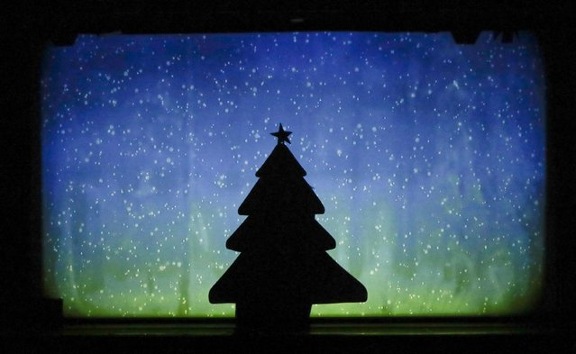 "In this photo taken on Tuesday, December 20, 2016, dancers of the U.S. company ""Catapult"" create a Christmas tree, during their show ""Magic Shadows"", in Milan, Italy. (Photo by Luca Bruno/AP Photo)"