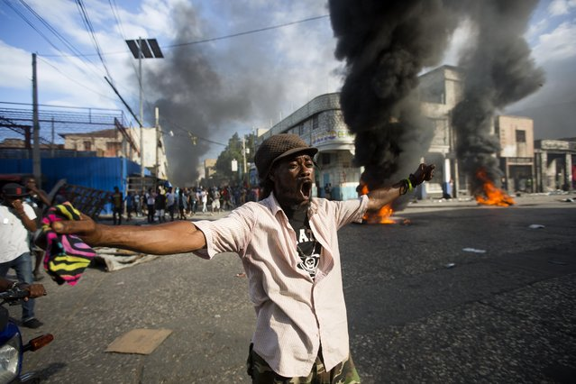 A demonstrator chants anti-government slogans during a protest demanding to know how Petro Caribe funds have been used by the current and past administrations, on the sidelines of events marking the 215th anniversary of independence Battle of Vertieres in Port-au-Prince, Haiti, Sunday, November 18, 2018. Much of the financial support to help Haiti rebuild after the 2010 earthquake comes from Venezuela's Petro Caribe fund, a 2005 pact that gives suppliers below-market financing for oil and is under the control of the central government. (Photo by Dieu Nalio Chery/AP Photo)