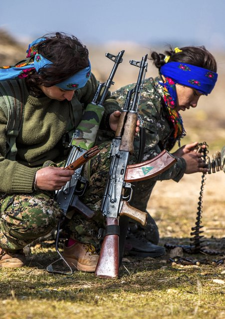 Female fighters of the Kurdish People's Protection Units (YPG) prepare their weapons as they participate in a military training in the western countryside of Ras al-Ain January 25, 2015. (Photo by Rodi Said/Reuters)