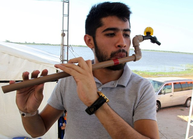 "A member of the Paraguayan youth orchestra ""Sonidos de la Tierra"" (Sounds of the Earth) performs with intruments made with recycled materials during the festival ""Somos H2O"" (We are H2O) to commemorate the World Water Day in Asuncion, Paraguay, 22 March 2015. (Photo by Andres Cristaldo/EPA)"