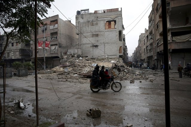 Residents ride a motorbike near rubble of damaged buildings in the town of Douma, eastern Ghouta in Damascus, Syria November 17, 2015. (Photo by Bassam Khabieh/Reuters)
