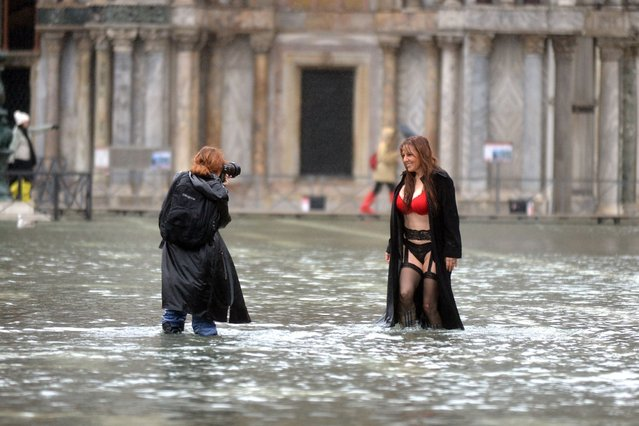 A woman poses on the flooded St. Mark's square during an acqua-alta (high-water) alert in Venice, on November 19, 2013. (Photo by Andrea Pattaro/AFP Photo)