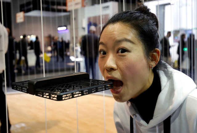 Xiao Huang of Zero Zero Robotics demonstrates the safety of the company's Hover Camera Passport drone by pretending to bite it during the 2017 CES in Las Vegas, Nevada, U.S., January 6, 2017. The light, foldable drone has blades that are enclosed and includes face-tracking and orbit technologies, she said. (Photo by Steve Marcus/Reuters)