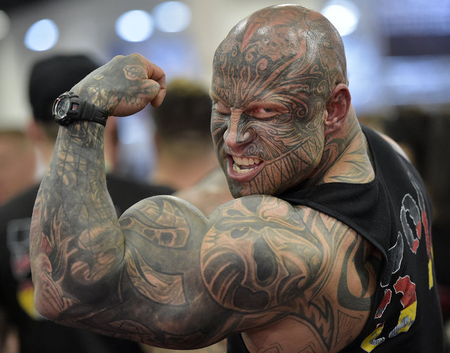 Bodybuilder Jens Dalsgaard from Denmark shows his muscles to visitors at the FIBO Power, a bodybuilding fair in Cologne, Germany, Thursday, April 9, 2015. (Photo by Martin Meissner/AP Photo)