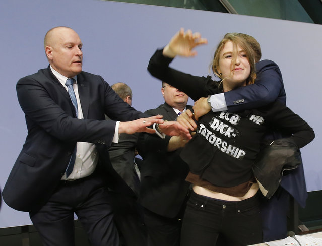 An activist is carried away after attacking ECB President Mario Draghi during a press conference of the European Central Bank, ECB, in Frankfurt, Germany, Wednesday, April 15, 2015. (Photo by Michael Probst/AP Photo)
