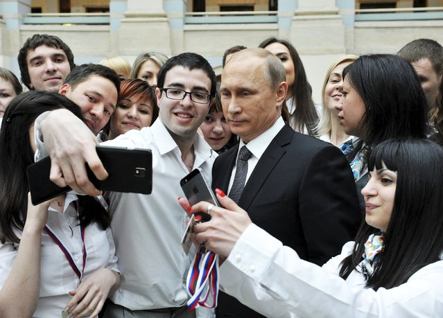 Russian President Vladimir Putin (3rd R, front) poses for a picture with call centre employees after a live broadcast nationwide call-in in Moscow April 16, 2015. (Photo by Mikhail Klimentyev/Reuters/RIA Novosti/Kremlin)