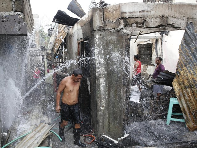 A man walks past busted water pipes at a residential district gutted by a fire in Muntinlupa, Metro Manila February 23, 2016. According to a local village leader Danilo Teves, more than 1000 people were rendered homeless and about 250 houses were gutted by a fire of unknown origin late Monday night in Soldiers Hills, Putatan Muntinlupa. (Photo by Erik De Castro/Reuters)