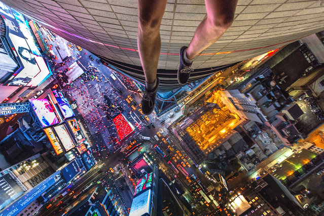Andrej Ciesielski dangels his legs off the side of a building overlooking Times Square, New York City. (Photo by Andrej Ciesielski/Caters News Agency)