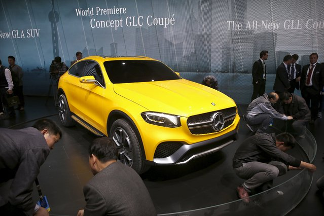 Workers prepare an exhibition stage next to a Mercedes Benz concept GLC Coupe during the 16th Shanghai International Automobile Industry Exhibition in Shanghai, April 20, 2015. (Photo by Aly Song/Reuters)
