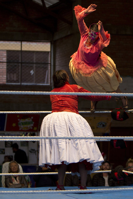 """Young cholita wrestler Nelly Pankarita jumps over her young rival Eleonor as they compete in the ring in El Alto, Bolivia, Sunday, February 24, 2019. """"I love those leaps of Reyna, and it's a dream that she's teaching us"""", said 17-year-old Nieves Laura Tarqui, who wrestles as Nelly Pankarita, a last name that means """"Little Flower"""" in Aymara. (Photo by Juan Karita/AP Photo)"""