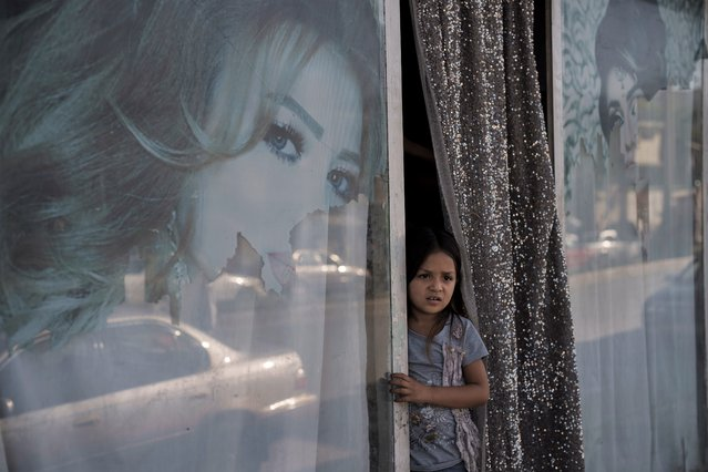 An Afghan girl looks out from a beauty salon in Kabul, Afghanistan, Thursday, September 16, 2021. Since the Taliban gained control of Kabul, several images depicting women outside beauty salons have been removed or covered up. (Photo by Felipe Dana/AP Photo)