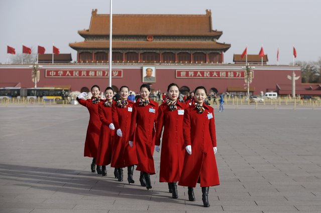 Hotel guides pose for pictures outside the Great Hall of the People during the opening session of the National People's Congress (NPC) in Beijing, China, March 5, 2016. (Photo by Aly Song/Reuters)