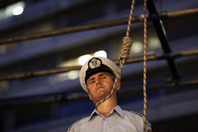 A police officer stands in a mock gallows outside the Finance Ministry during a protest against budget cuts  in Athens, on September 6, 2012. (Photo by Kostas Tsironis/AFP Photo)