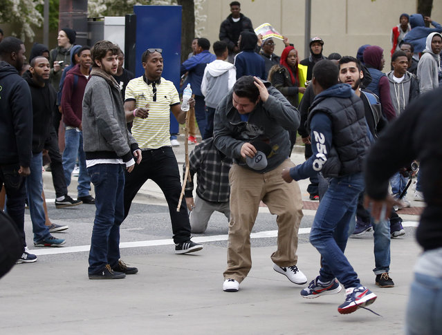 A man, center, shields himself after being struck after a march to City Hall for Freddie Gray, Saturday, April 25, 2015 in Baltimore. (Photo by Alex Brandon/AP Photo)