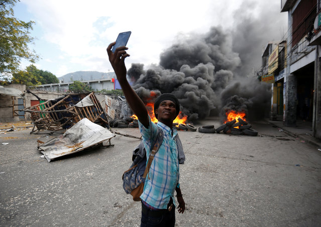 A man takes a selfie next to a burning barricade during a protest against the government in the streets of Port-au-Prince, Haiti, February 10, 2019. (Photo by Jeanty Junior Augustin/Reuters)