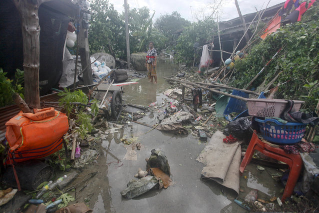 A Thai woman stands amid debris in the aftermath of Tropical Storm Pabuk Saturday, January 5, 2019, in Pak Phanang, in Thailand's southern province of Nakhon Si Thammarat. The storm damaged houses, knocked down power lines and triggered flash floods in several east coast provinces. (Photo by Sumeth Panpetch/AP Photo)